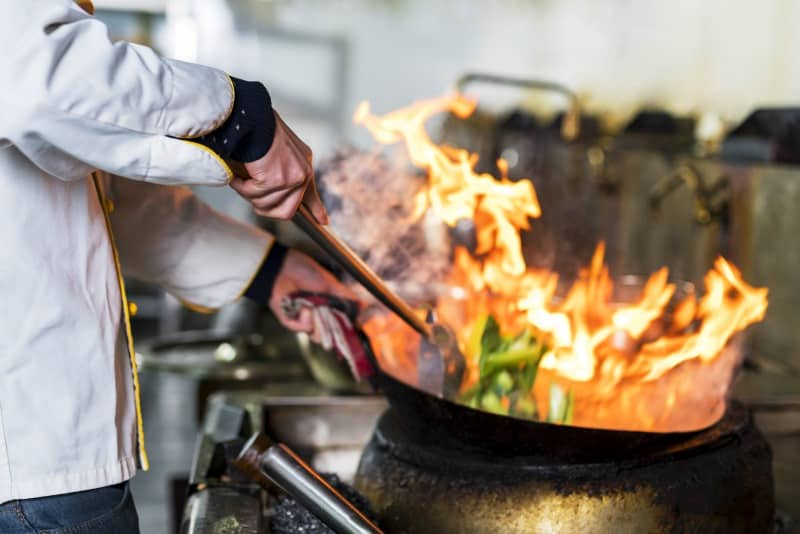 Chef stirring food in wok over flames