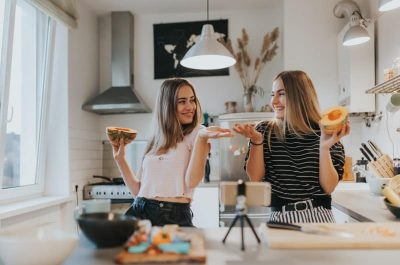 Two female friends joking around and eating fruit in a kitchen