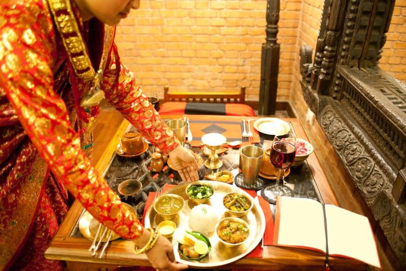 Waitress in Indian restaurant setting down platter of food on table