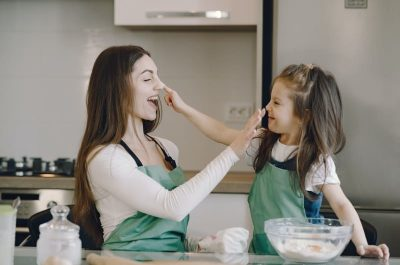 Mom and daughter, being silly, putting flour on each other's nose in a kitchen