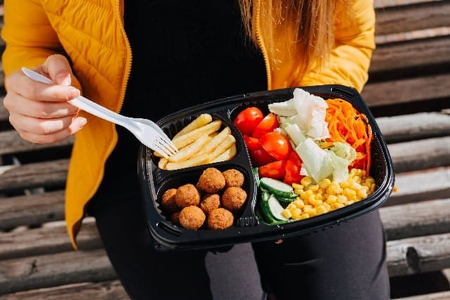 man holding to-go container of food